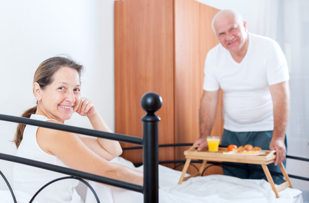 breakfast in bed: Husband and wife having breakfast in bed. Stock Photo