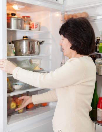 refrigerator kitchen: woman checking   food in   refrigerator at  kitchen. Stock Photo
