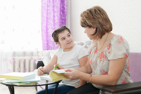 teaching adult: Mature mother helping her child with homework at home.