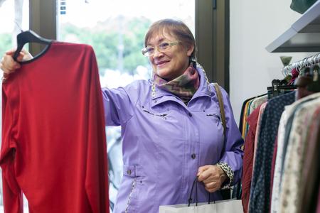 personas de pie: Mujer madura elegir blusa en una tienda de ropa. Foto de archivo