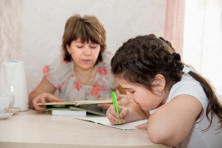 ni�os ayudando: Mam� e hija hacer la tarea en casa. Foto de archivo