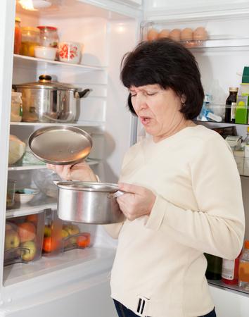 refrigerator kitchen: Adult housewife standing at   kitchen near   refrigerator.
