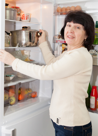refrigerator kitchen: Adult housewife standing at   kitchen near   refrigerator.