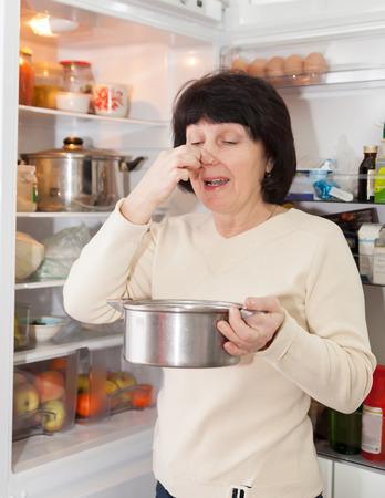 refrigerator kitchen: woman checking   food in   refrigerator at  kitchen. Stock Photo