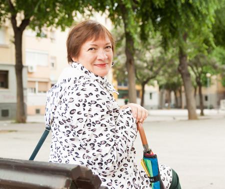 happy seasonable: mature woman in jacket outdoors in autumn