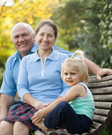 grandaughter: elderly grandparents with cutes grandchild    in autumn park. Stock Photo