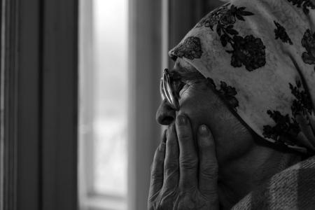 grandmother: Old grandmother  near window in  room.