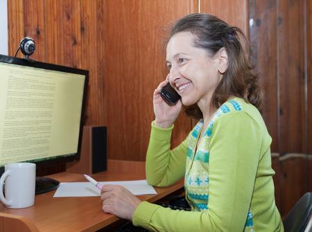 casua: Mature woman talking on   mobile phone near   computer