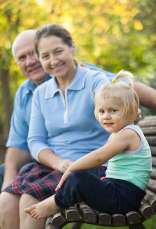 grandaughter: elderly grandparents with cutes grandchild     in autumn park.