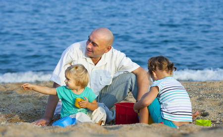3 4 years: Children with Dad on  beach  at summer day. Stock Photo