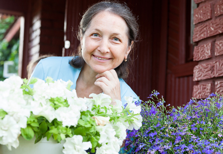 Happy middle-aged woman resting on   porch of   house. Stock Photo