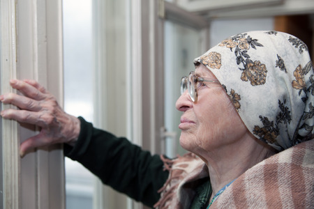 looking aside: Lonely grandma in   scarf and glasses looking aside. Stock Photo