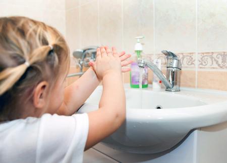 lavarse las manos: la niña lavándose las manos por el lavabo en el baño