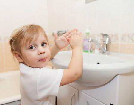 lavarse las manos: muchacha que se lava las manos con jabón por el fregadero