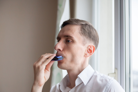 harmonica: young man in   white shirt playing harmonica. Stock Photo