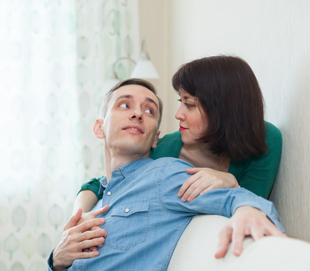 couple on couch: Lovely young couple on   couch at home.