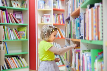 Bambina nella biblioteca dei bambini. Archivio Fotografico