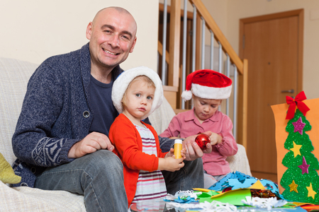 Girls with Dad on   couch doing holiday crafts. photo