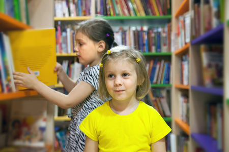 Two little sisters in children's library.