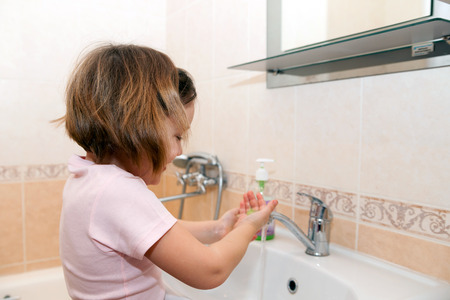 niña se lava las manos con jabón por el fregadero