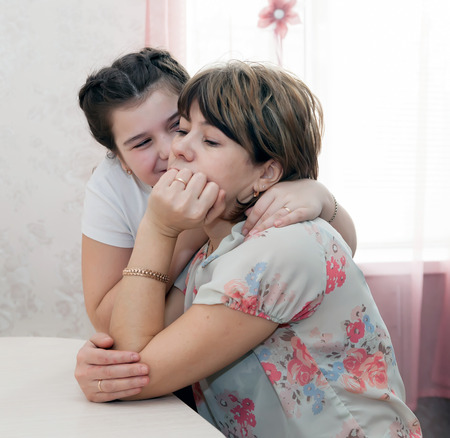 Teen daughter calming  sad mother Stock Photo