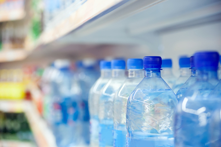 Showcase with bottles of water at  store.