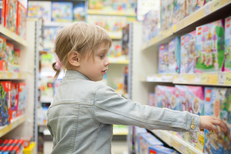 child in   toy store choosing   purchase 版權商用圖片