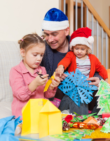 Cheerful Daughter and dad making decorations for Christmas