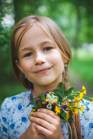 Portrait of   8 years old girl in   park with flowers