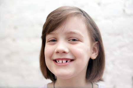 Portrait of   smiling seven year old girl on   white background.