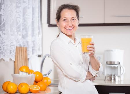 smiling middle-aged woman preparing orange juice in   kitchen