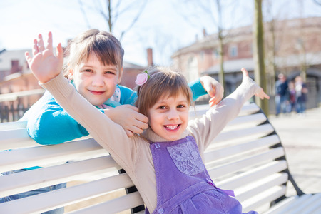 Portrait of girlfriends of 7 and 5 years old on   bench in   spring park.