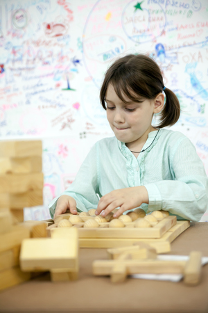 girl of 7 years old playing  with wooden puzzle.