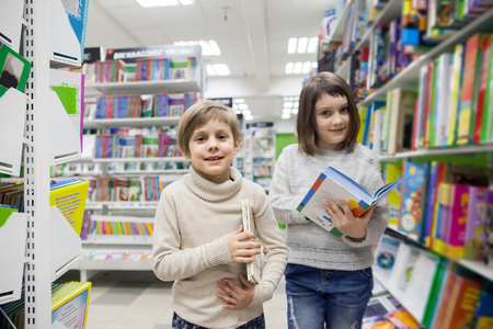 Portrait of   girls of 8 and 6 years in shop choosing books