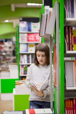 first grader  choosing   books in   bookstore for school Banco de Imagens