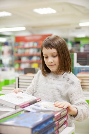 first grader  choosing   books in   bookstore for school Stockfoto