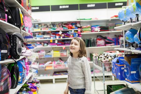 first grader choosing briefcase in store for school