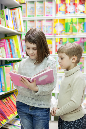 Two little girls reading  books  at   store