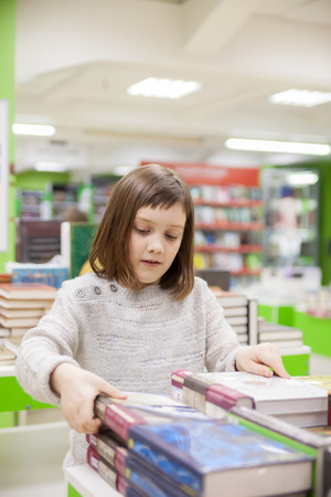 Portrait of   girl  of 8   years  choosing books in   bookstore