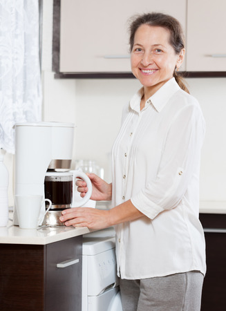 mature woman preparing coffee in   white coffee maker. 写真素材 - 119965683