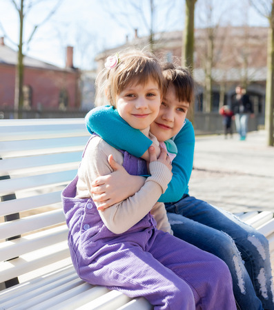 Portrait of girlfriends  on   bench in   spring park. Stock Photo