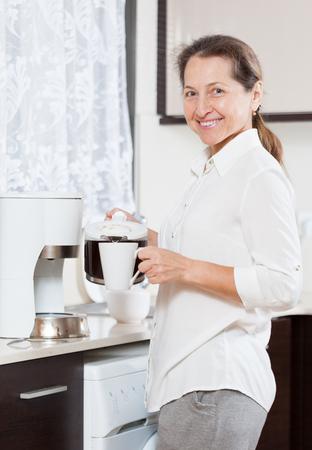 mature woman preparing coffee in   white coffee maker. Stock Photo