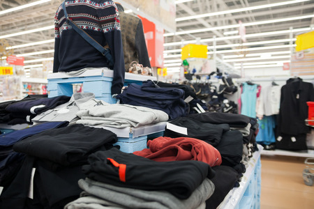 Many different clothes   on   shelves in   store.