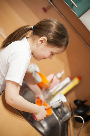 Cute schoolgirl   washing   plate in   kitchen. Stock Photo