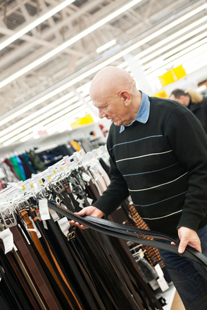 Mature bald man in   clothing store.