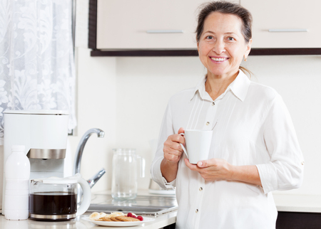 Portrait of   nice elderly woman in   kitchen with   cup of coffee and cookies. Stock Photo