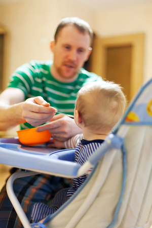 father feeding   small child with vegetable puree behind   childrens chair.