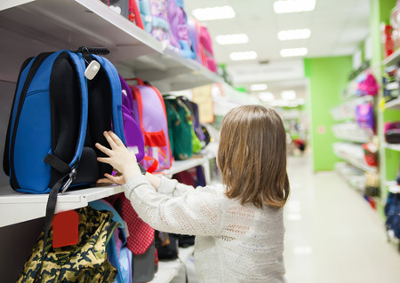 Porträt eines Mädchens von 8 Jahren im Geschäft, das Aktentasche für die Schule wählt Standard-Bild