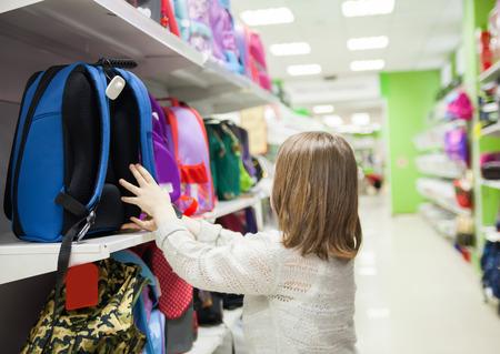 Portrait of   girl of 8 years in shop choosing  briefcase  for school Zdjęcie Seryjne