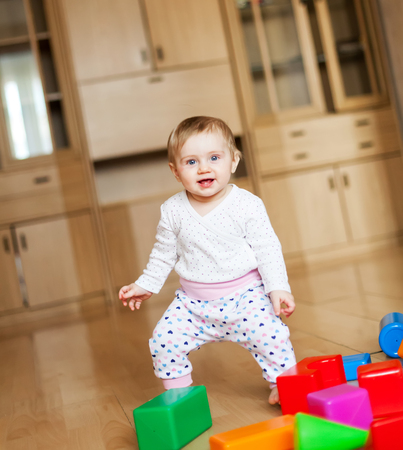 Baby with multi-colored designer at home on   floor Stock Photo